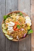 Malaysian style maggi goreng mamak  or spicy dried curry instant noodles.  Asian cuisine, ready to serve on wooden dining table setting. Fresh hot with steamed smoke.