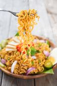Spicy fried curry instant noodles or Malaysian style maggi goreng mamak.  Ready to serve on wooden d