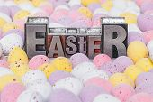 The word Easter in old metal letterpress surrounded by candy covered mini chocolate eggs.