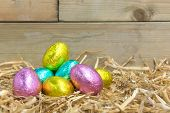 Foil covered chocolate Easter eggs in a straw nest in a barn
