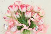 Tulip flower arrangement with easter eggs and ribbon curl over handmade paper background.