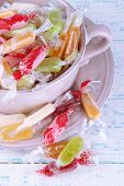 Tasty candies in bowl on wooden background
