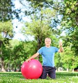 Man in sportswear sitting on an exercising mat in park and giving thumb up shot with tilt and shift