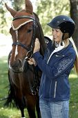 Female rider in equestrian helmet caressing horse, smiling.