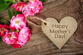 stock photo of gratitude  - Heart shaped mothers day card with roses on wood background - JPG