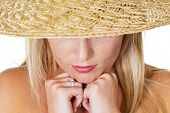a young pensive woman with straw hat. portrait against white background