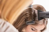 stock photo of blow-up  - Drying long brown hair with hair dryer and round brush.