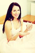 Prtrait of a beautiful young woman in bed, holding pills and a glass of water, smiling to the camera
