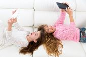 Children friends kid girls having fun playing with tablet pc lying on white sofa
