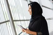 stock photo of muslim  - side view of smiling muslim woman with tablet computer - JPG