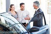 image of showrooms  - mature salesman showing new car to a couple in showroom - JPG