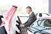 Arabian man getting in a new car for test drive at vehicle dealership