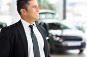 image of showrooms  - confident vehicle dealership salesman in showroom - JPG