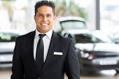 happy young indian car salesman in showroom