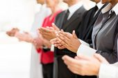 group of businesspeople clapping hands during meeting presentation
