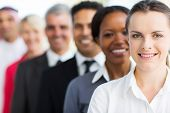 smiling businesswoman with colleagues standing in a row