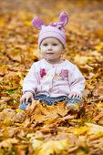 Laughing kind sitting on yellow leaves
