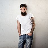 Portrait of tattooed bearded man wearing blank t-shirt
