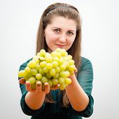 Cute young girl with green grapes