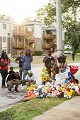 FERGUSON, MO/USA - AUGUST 30, 2014: A crowd gathers at makeshift memorial near where black teenager Michael Brown was shot to death by police in Ferguson, Missouri.