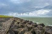 foto of dike  - Dike along a lake in summer under a cloudy sky - JPG