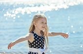 stock photo of debonair  - Cute little girl playing on the coast of the river - JPG