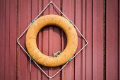 Old Orange Lifebuoy Hanging On Red Wall