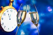 New Year Or Christmas At Midnight With Champagne Flutes Make Cheers Blue Bokeh And Clock