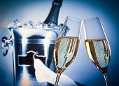 Champagne Flutes With Golden Bubbles In Front Of Champagne Bottle In Bucket