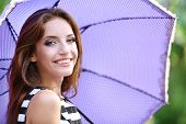 Beautiful young girl with umbrella outdoors
