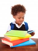 Portrait of sweet little black boy reading books isolated on white background, preparation to go to