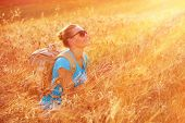 Beautiful traveler girl enjoying golden wheat field in sunset light, beautiful summer nature, farmla