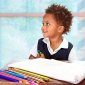 Portrait of cute little African preschooler on drawing lesson, painting with many colorful pencils,