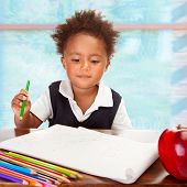 Portrait of cute little African preschooler on drawing lesson, have big fresh red apple for lunch in