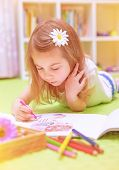 Preschooler girl painting with colorful pencil, lying down on the floor in daycare and enjoying art,