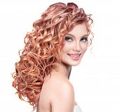 Beauty girl with red curly hair. Healthy and long permed Blonde Wavy hair. Beautiful smiling young w