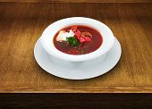Delicious ukrainian borscht served on a white plate. Hot soup with beet and sour cream on wooden table in restaurant