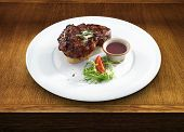 Healthy well done meat steak with butter and herbs served with berry and wine sauce and fresh vegetables on a white round plate