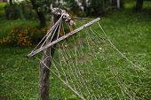 old hammock hanging in the garden