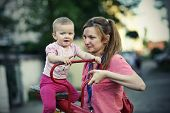 image of seesaw  - Small girl with her mother playing on the seesaw - JPG