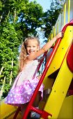 Little Girl Is Climbing Up On Ladder In Playground Equipment