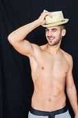 stock photo of half naked  - Handsome man half naked with hat smiling on black backgound - JPG