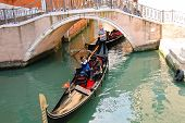 Gondolier Sailing With Tourists In A Gondola Along One Of The Canals In Venice, Italy