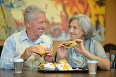 Elderly couple eating fast food