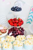 Berries, popcorn and canapes on a dessert table at party