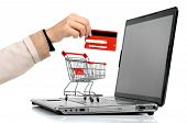 image of grocery cart  - Laptop with small shopping cart and a hand with credit card isolated in white - JPG
