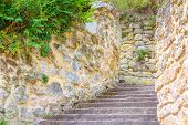Wooden Staircase Between Stone Walls.