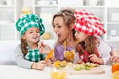 pic of child feeding  - Woman and little girls preparing a fruit salad - JPG