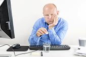 Overworked office worker taking pills for headache