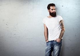 stock photo of macho man  - Portrait of tattooed bearded man wearing blank t - JPG